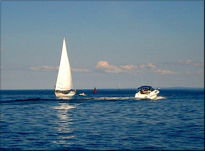 Sailboat and Powerboat passing at the harbor's mouth