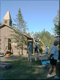 A Loader lifts shingles to the Church Roof